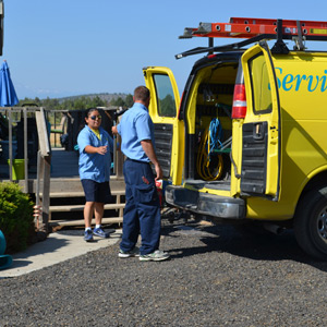 Two ServiceMaster technicians grabbing equipment from a ServiceMaster branded van before beginning a fire damage restoration service