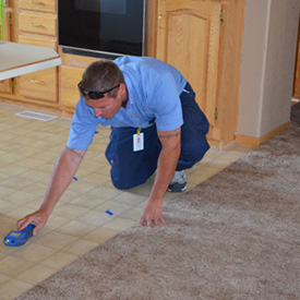 ServiceMaster technician assessing water damage to a tile floor