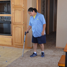 ServiceMaster technician assessing water damage to carpet flooring