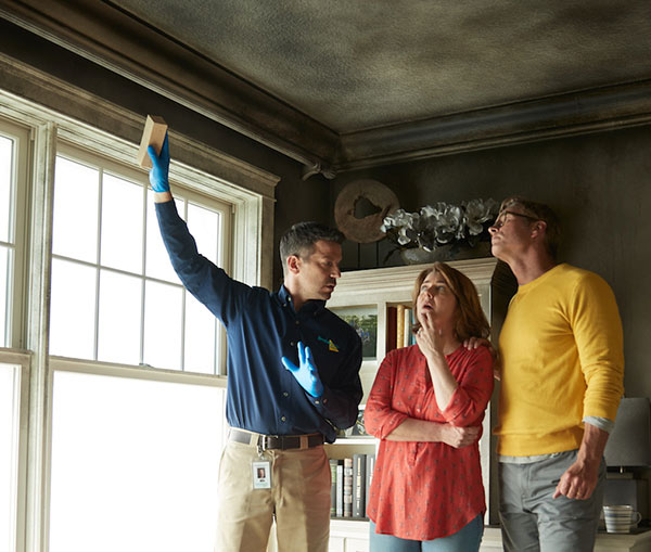 A ServiceMaster technician explaining the fire damage restoration process to two customers on-site